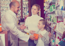 Mature male pharmacist helping customers. Mature male pharmacist wearing white coat standing next to shelves with medicine and helping customers Stock Images