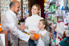 Mature male pharmacist helping customers. Mature male pharmacist wearing white coat standing next to shelves with medicine and helping customers Royalty Free Stock Photos