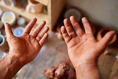 Mature male potter showing his palms while molding a clay in pottery workshop, close-up, selective focus. Creative work process. Craftsman preparation for Stock Images