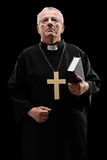 Mature male priest holding a holy bible. On black background Royalty Free Stock Photo
