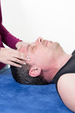 Mature male receiving ear reflexology massage of both temples Royalty Free Stock Photography