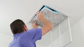 Man Replacing Ceiling Air Filter stock video footage
