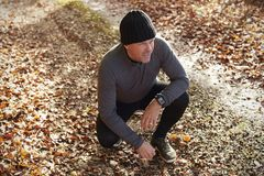 Mature Male Runner Pausing For Breath During Exercise In Woods Royalty Free Stock Photos
