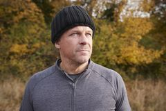 Mature Male Runner Pausing For Breath During Exercise In Woods Stock Images