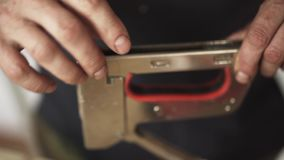 Mature male`s hands are holding staple gun and loading it with staples. Mature male`s hands are holding big metallic staple gun over wooden plank and loading it stock video footage