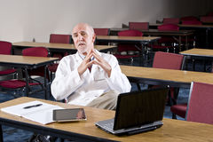 Mature male scientist sitting in conference room. Mature male scientist wearing lab coat sitting in conference room Royalty Free Stock Image