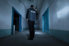 Security Guard Standing In Corridor Of Building. Mature Male Security Guard With Flashlight Standing In Corridor Of The Building Royalty Free Stock Images