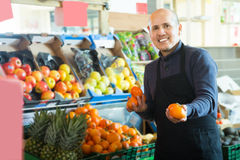 Mature male seller offers mandarins Royalty Free Stock Image