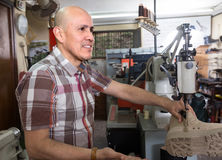 Mature male sewing leather boots on stitch lathe Stock Images