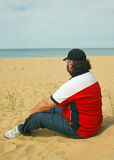 Mature Male Sitting on Beach. Looking to the horizon Royalty Free Stock Photography