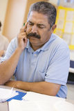 Mature male student frowning in class.  Royalty Free Stock Photography