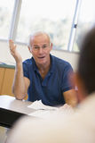 Mature male student gesturing in class Royalty Free Stock Photos