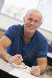 Mature male student holding glasses in class Royalty Free Stock Images