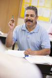Mature male student raising hand in class Stock Photo