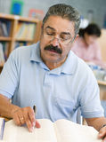 Mature male student studying in library.  Royalty Free Stock Image