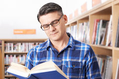 Mature Male Student Studying In Library. Mature Male Student Studying Book In Library Stock Image