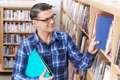 Mature Male Student Taking Book From Shelf In Library. Mature Male Student Takes Book From Shelf In Library Stock Photo