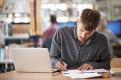 Mature Male Student Working On Laptop In College Library Royalty Free Stock Photos