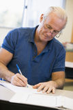 Mature male student writing in class Stock Image