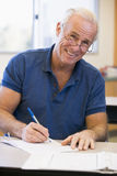 Mature male student writing in class.  Royalty Free Stock Photo
