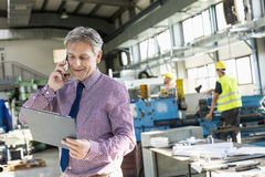Mature male supervisor looking at clipboard while talking on mobile phone in industry.  Stock Image