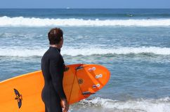Mature male surfer looks at waves. A mature male surfer age range 40`s to 50`s wearing a black wet suit looks at the waves on Carlsbad State Beach in California Stock Photo
