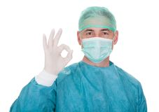Mature male surgeon gesturing ok sign. Over White Background Royalty Free Stock Images