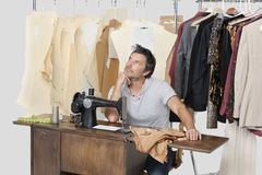 Mature male tailor thinking while sitting at sewing machine with fabric stock photo