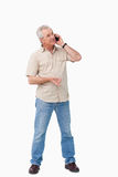Mature male talking on his cellphone. Against a white background Royalty Free Stock Images