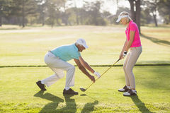 Mature male teaching woman to play golf Royalty Free Stock Photos