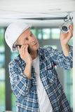 Mature male technician installing camera on phone. Mature male technician installing camera on the phone Stock Photos