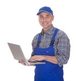 Mature male technician using laptop. Over White Background Stock Photo