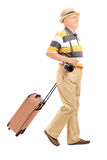 Mature male tourist carrying his baggage. Isolated on white background Royalty Free Stock Photo