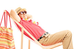 Mature male tourist enjoying on a beach chair Royalty Free Stock Images