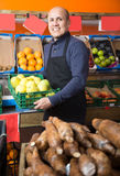 Mature male vendor selling apples in the grocery store. Friendly mature male vendor selling apples in the grocery store Royalty Free Stock Image