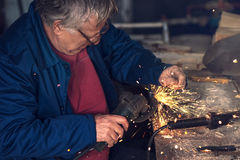 Mature male worker grinding metal in workshop. Mature male worker grinding piece of metal with grinder tool in workshop without protective equipment Stock Images