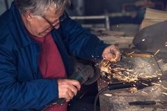 Mature male worker grinding metal in workshop. Mature male worker grinding piece of metal with grinder tool in workshop without protective equipment Royalty Free Stock Photos