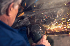 Mature male worker grinding metal in workshop. Mature male worker grinding piece of metal with grinder tool in workshop without protective equipment Royalty Free Stock Photography