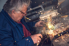 Mature male worker grinding metal in workshop. Mature male worker grinding piece of metal with grinder tool in workshop without protective equipment Royalty Free Stock Photo