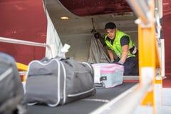 Worker Placing Baggage On Conveyor To Unload Airplane. Mature male worker placing baggage on conveyor to unload airplane royalty free stock photography