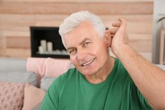 Mature man adjusting hearing aid. At home stock images