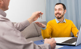 Mature man and agent occupational lease. Adult men and agent sign contract of rent apartments and hand over keys stock photography