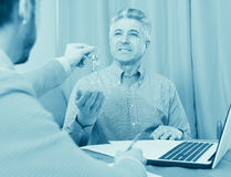 Mature man and agent occupational lease. Adult men and agent sign contract of rent apartments and hand over keys stock images