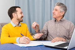 Mature man and agent occupational lease. Mature men and young agent sign contract of rent apartments and hand over keys royalty free stock image