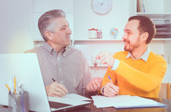 Mature man and agent sign rental agreement. Adult men and agent sign lease contract of apartment at office and hand over keys royalty free stock photos