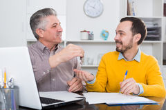 Mature man and agent sign rental agreement. Man and lease agent sign lease contract of apartment at office and hand over keys stock image