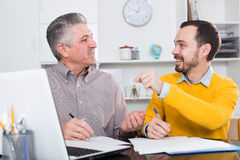 Mature man and agent sign rental agreement Stock Photo