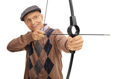 Mature man aiming with a bow and arrow. Isolated on white background royalty free stock photography