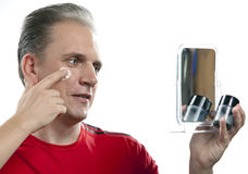 The mature man applies the cream which is looking after face skin Royalty Free Stock Image