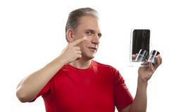 The mature man applies the cream which is looking after face skin Royalty Free Stock Photos